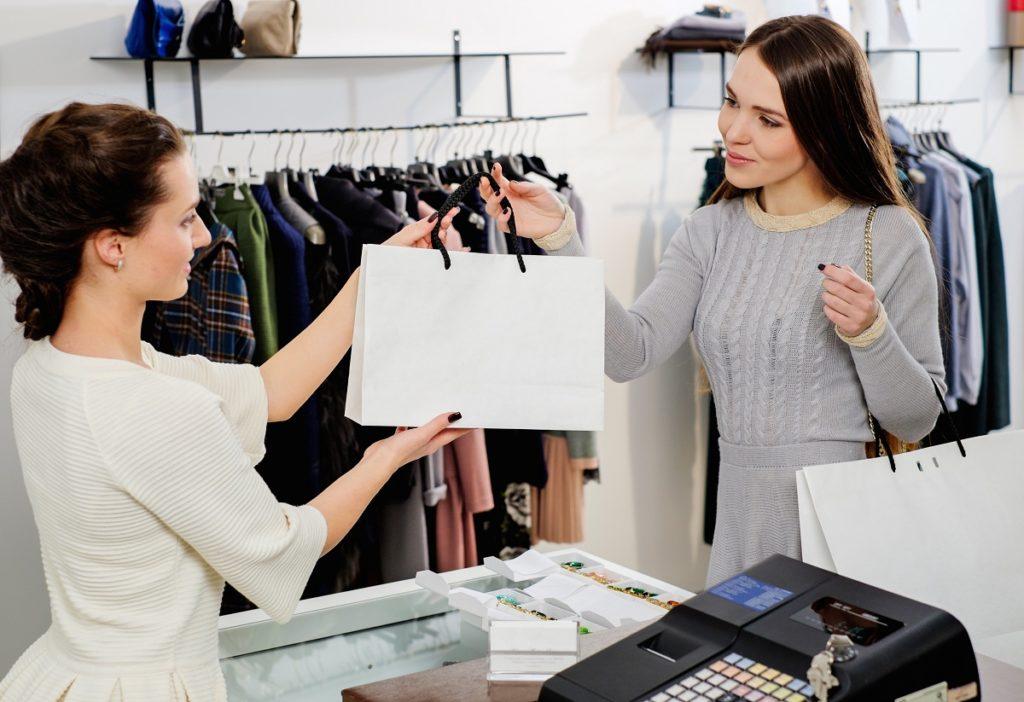 Employee handing shopping bag